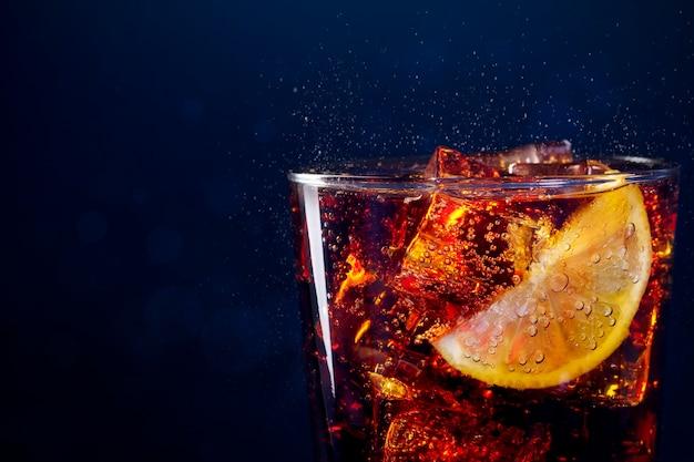 Close de um copo de bebida fresca com cubos de gelo e rodelas de limão