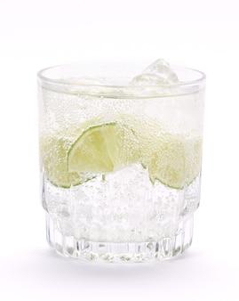 Close de um coquetel com água com gás, fatias de limão e cubos de gelo em uma superfície branca