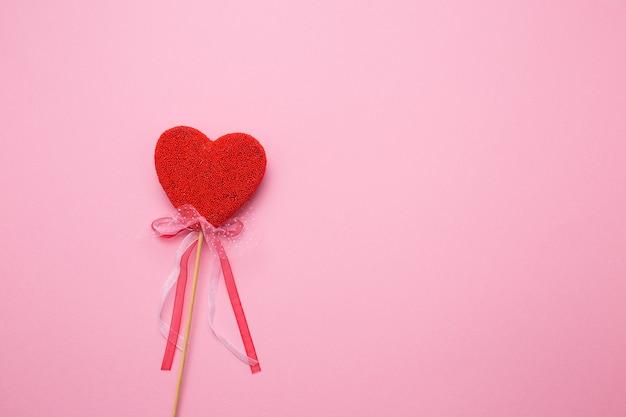 Close de um coração com uma decoração em uma vara em um fundo rosa isolado. soletre amor em letras brancas.