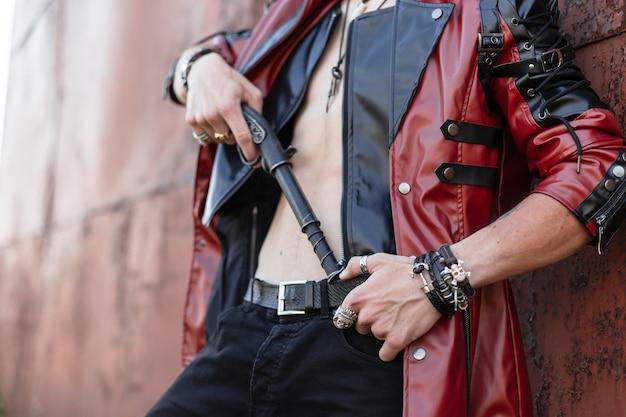 Close de um corpo masculino com um torso nu em uma jaqueta de couro elegante em jeans com arma vintage. cara com roupas da moda se passando perto de uma parede enferrujada. estilo antiquado.