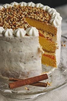 Close de um delicioso bolo branco de natal fatiado com nozes e tangerina