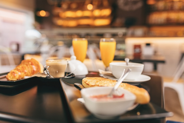 Close de um delicioso café da manhã, inclui suco de laranja, pão torrado e um croissant