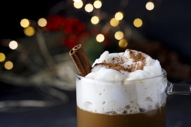 Close de um delicioso café de natal com canela e espuma, na frente das luzes do bokeh