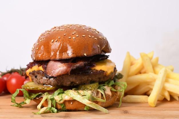 Close de um delicioso hambúrguer de carne em uma placa de madeira com batatas fritas e tomates