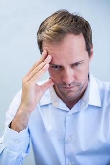 Close de um dentista tenso sentado com a mão na testa
