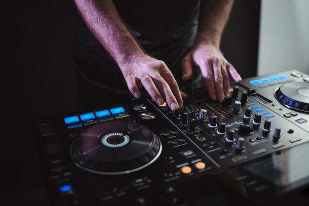 Close de um dj masculino trabalhando sob as luzes contra um fundo escuro em um estúdio
