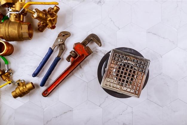 Close de um dreno em dispositivos elétricos de chave inglesa e encanadores de quarto de banho