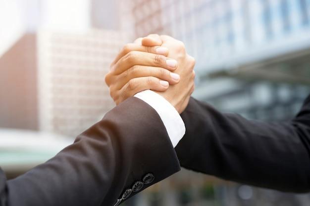 Close de um empresário apertando a mão de um investidor entre dois colegas