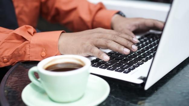 Close de um empresário asiático digitando em um laptop