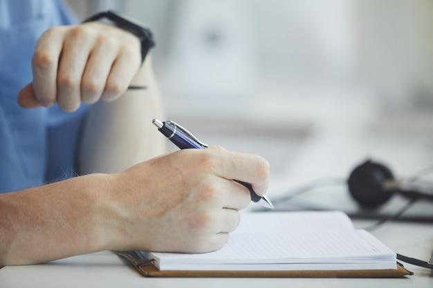 Close de um empresário fazendo anotações em um bloco de notas na mesa em que ele está planejando seu negócio