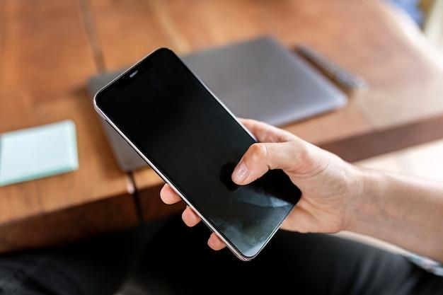 Close de um empresário usando um telefone celular