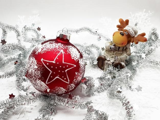 Close de um enfeite de natal vermelho com guirlandas em uma superfície branca