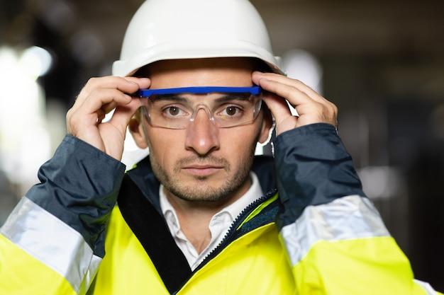Close de um engenheiro profissional sério e confiante olhando para a câmera usando uniforme de segurança
