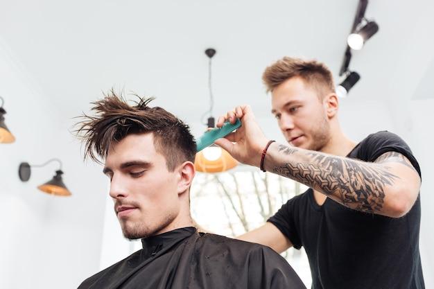 Close de um estiloso penteado masculino e um corte de cabelo em uma barbearia ou salão de cabeleireiro