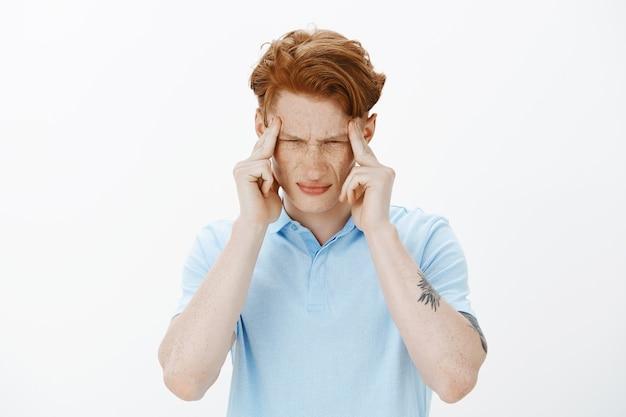 Close de um estudante universitário ruivo angustiado tentando se concentrar, sentindo tonturas, com dor de cabeça