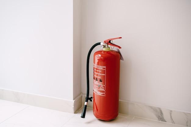 Close de um extintor de incêndio vermelho no chão, no canto, contra uma parede branca
