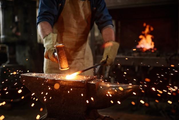 Close de um ferreiro forjando manualmente o metal fundido na oficina