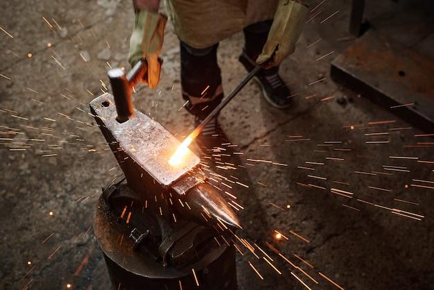 Close de um ferreiro usando um martelo para forjar os detalhes de ferro na ferraria
