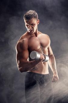 Close de um fisiculturista de homem atlético poder bonito fazendo exercícios com halteres. corpo musculoso de aptidão em fundo escuro de fumaça. macho perfeito. incrível fisiculturista, tatuagem, posando.