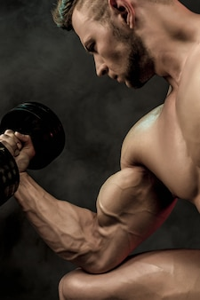 Close de um fisiculturista de homem atlético poder bonito fazendo exercícios com halteres. corpo musculoso de aptidão em fundo escuro. foco seletivo. incrível fisiculturista, posando.