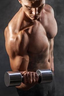 Close de um fisiculturista de homem atlético poder bonito fazendo exercícios com halteres. corpo musculoso de aptidão em fundo escuro. foco seletivo. incrível fisiculturista, tatuagem, posando.