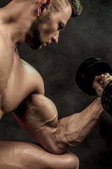Close de um fisiculturista de homem atlético poder bonito fazendo exercícios com halteres. corpo musculoso de aptidão em fundo escuro.