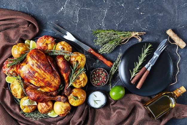 Close de um frango assado inteiro servido em uma travessa preta com maçãs assadas e ervas aromáticas em uma mesa de concreto