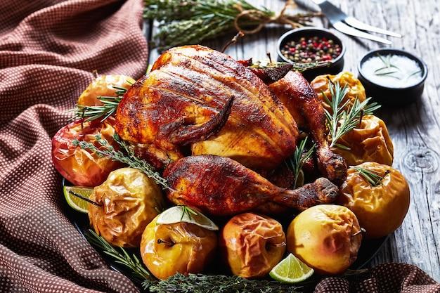 Close de um frango assado inteiro servido em uma travessa preta com maçãs assadas e ervas aromáticas em uma mesa de madeira rústica
