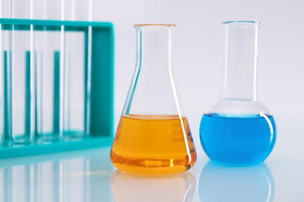Close de um frasco erlenmeyer com líquido laranja e um frasco redondo com líquido azul em um laboratório
