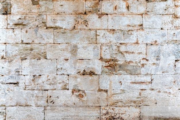 Close de um fundo de textura de parede de pedra de tijolos brancos antigos