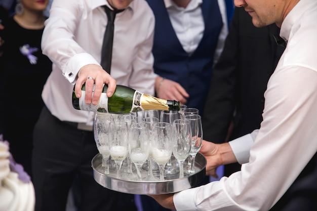 Close de um garçom enchendo copos com champanhe