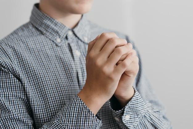 Close de um garotinho orando