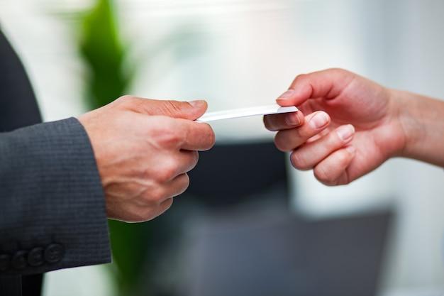 Close de um gerente dando seu cartão de visita a um cliente