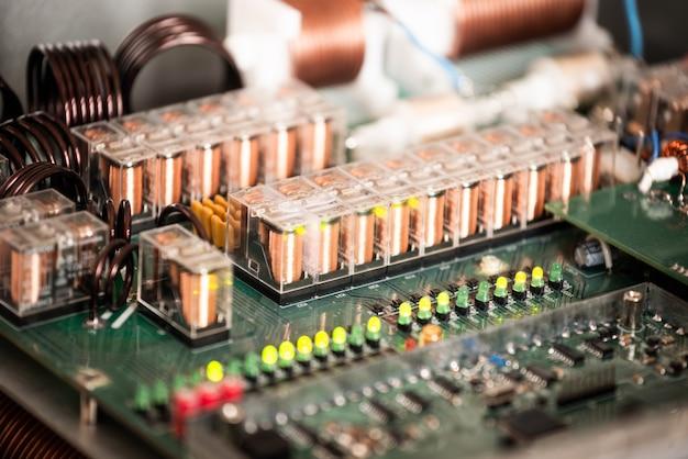 Close de um grande microcircuito verde com fios e plugues conectados a ele em uma fábrica de equipamentos militares