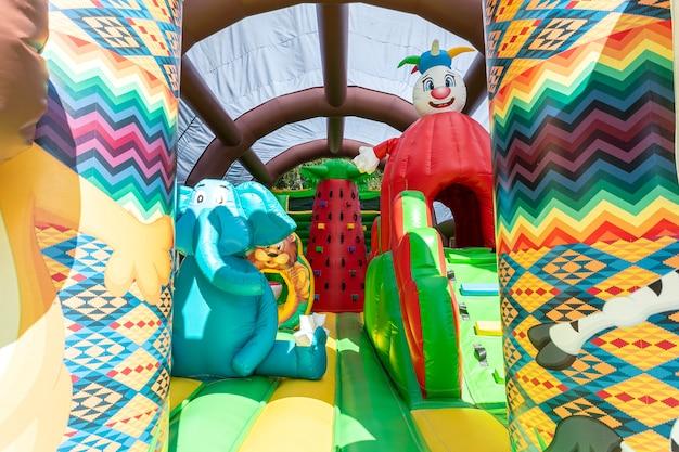 Close de um grande trampolim inflável com um leão e um elefante no parquinho