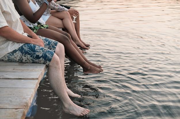 Close de um grupo de amigos sentado em um píer e molhando os pés na água em um dia de verão