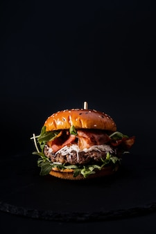 Close de um hambúrguer de aparência saborosa isolado em uma superfície preta