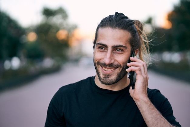 Close de um homem adulto de cabelos compridos caminhando na rua enquanto faz uma ligação comercial