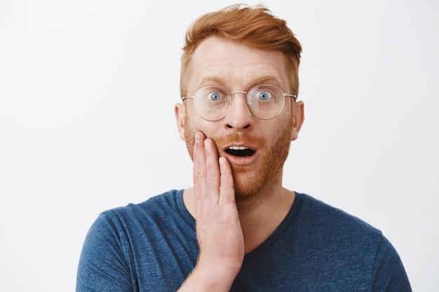 Close de um homem adulto ruivo surpreso de óculos reagindo a algo incrível