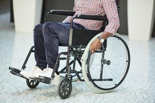Close de um homem africano com deficiência, andando em uma cadeira de rodas ao longo do corredor