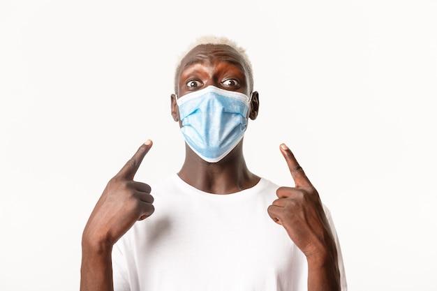 Close de um homem afro-americano bonito alegre, usando uma máscara médica