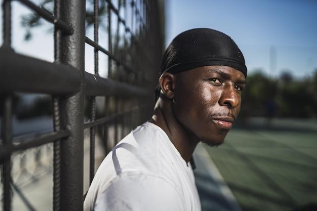 Close de um homem afro-americano com uma camisa branca encostado em uma cerca na quadra de basquete