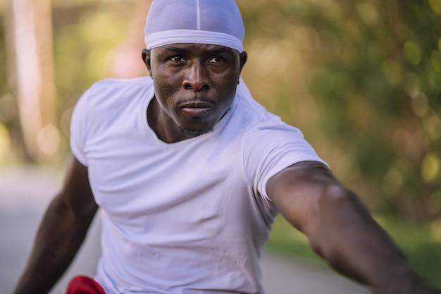 Close de um homem afro-americano com uma camisa branca se espreguiçando no parque