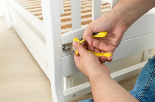 Close de um homem apertando os parafusos na mobília com uma chave de fenda