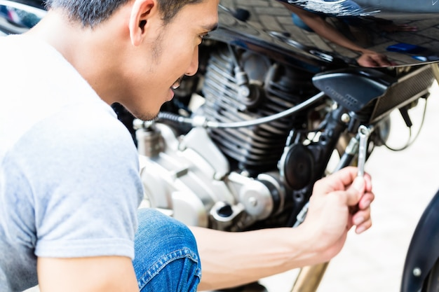 Close de um homem asiático fazendo manutenção de uma motocicleta