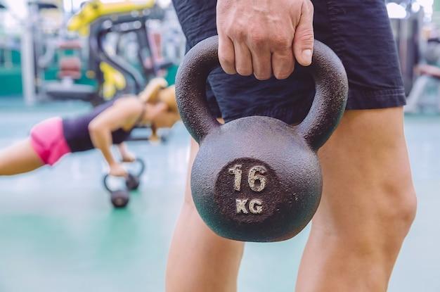 Close de um homem atlético segurando um kettlebell de ferro preto e uma mulher fazendo flexões sobre kettlebells em um treinamento crossfit