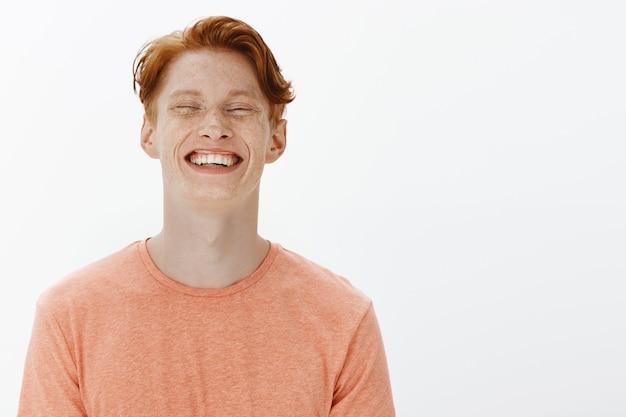 Close de um homem atraente e despreocupado rindo e sorrindo, se divertindo