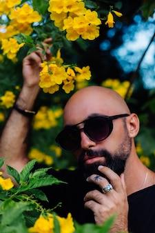 Close de um homem barbudo bronzeado e brutal em óculos de sol com uma tatuagem de palmeira no dedo rodeado por flores amarelas no parque