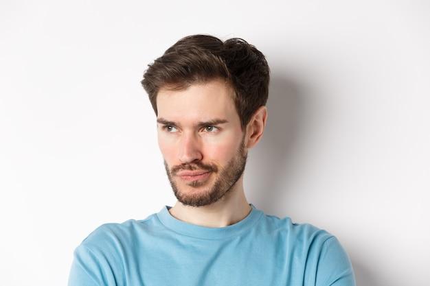 Close de um homem barbudo decepcionado, emburrado e olhando para a esquerda com uma expressão pensativa, em pé sobre um fundo branco
