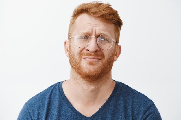 Close de um homem barbudo ruivo triste e miserável de óculos, choramingando e parecendo chateado